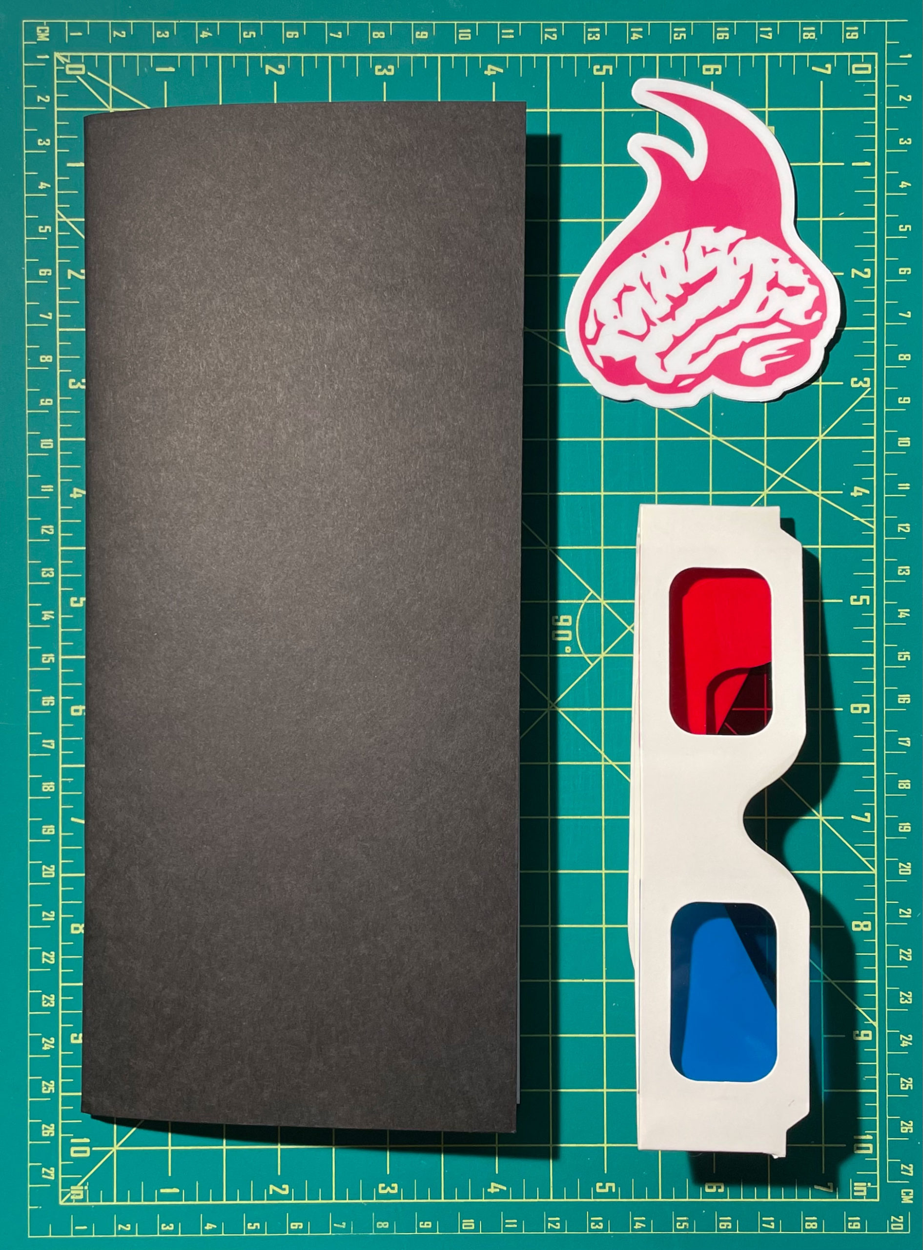 A black, rectangular zine is pictured next to a sicker of the Grey Matter Gravy logo and a pair of 3D glasses.